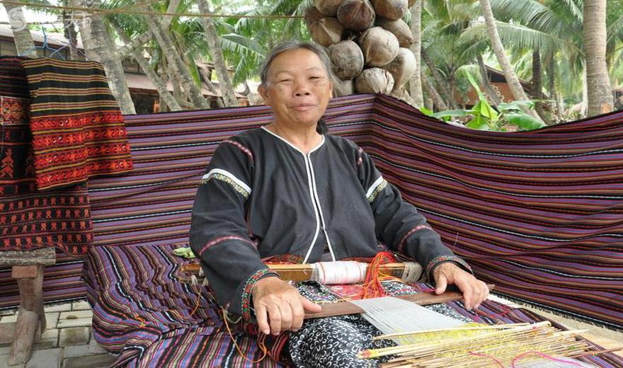 椰田古寨中为游人展示黎族织锦技艺的阿婆
